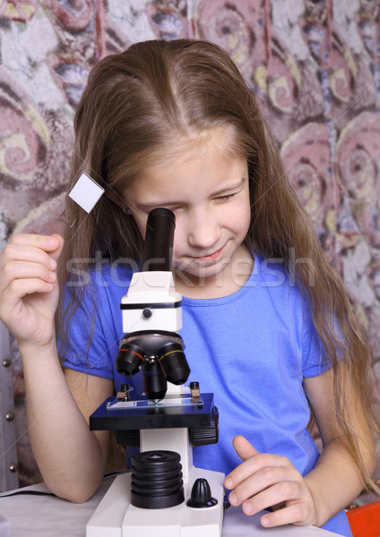 Girl looking through a microscope  Stock photo © krugloff