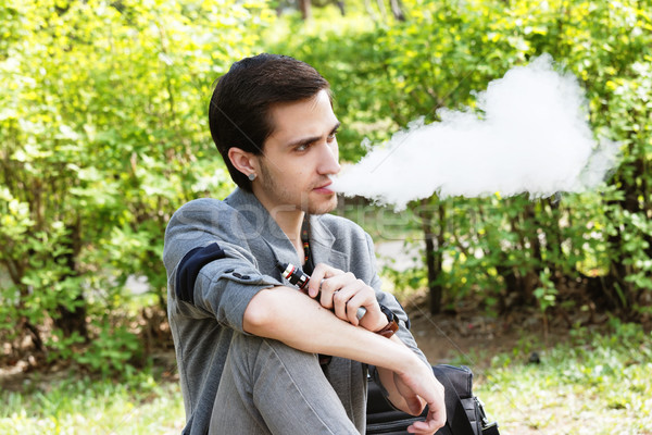 Thoughtful young businessman smokes a vape in a park Stock photo © krugloff