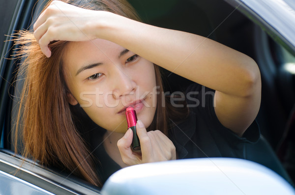 Stock photo: Asian girl applying makeup while in the car