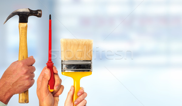 Hand of handyman with a hammer and screwdriver. Stock photo © Kurhan