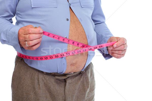 Fat man measuring his big stomack. Stock photo © Kurhan