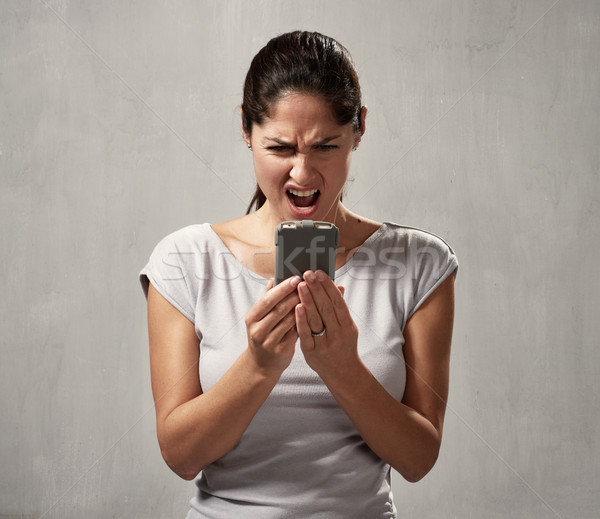 surprised uncontented woman with smartphone Stock photo © Kurhan