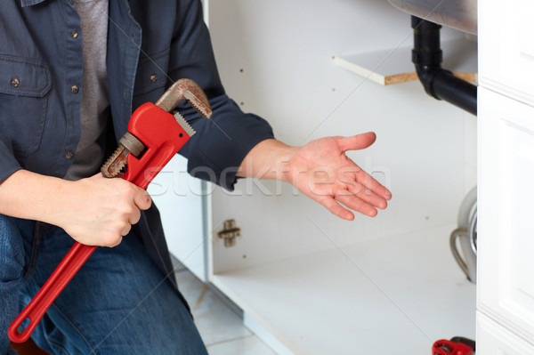 Plumber hands with wrench. Stock photo © Kurhan