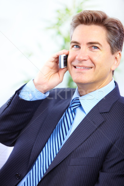 Handsome smiling businessman calling by cellular in the office