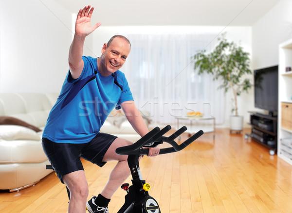 Senior Man cycling on bike trainer. Stock photo © Kurhan