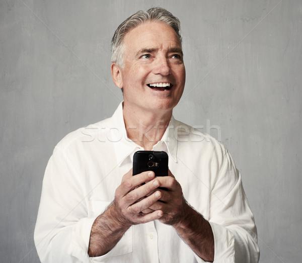 Smiling senior man with smartphone Stock photo © Kurhan