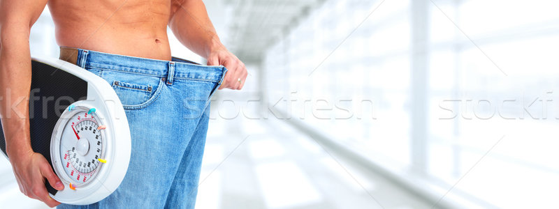 Slimming man wearing big pants over blue background. Stock photo © Kurhan