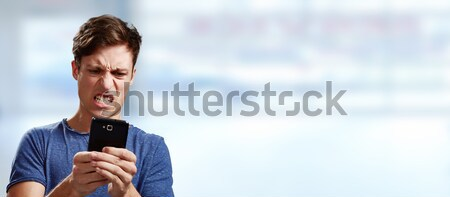 Zangado homem moço azul telefone Foto stock © Kurhan