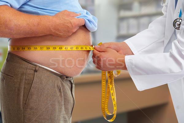 Doctor measuring obese man stomach. Stock photo © Kurhan