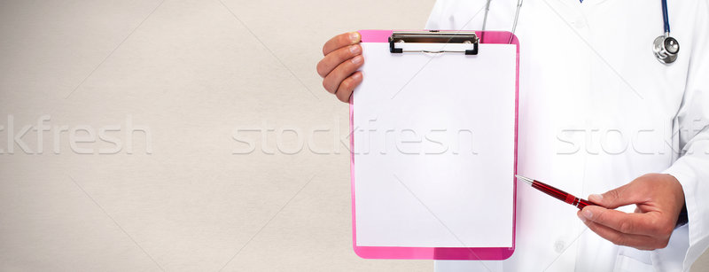 Hands of medical doctor with a clipboard. Stock photo © Kurhan