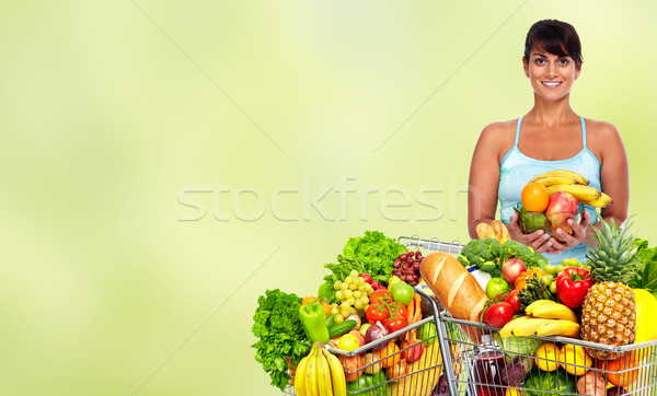 Happy young woman with grocery shopping cart. Stock photo © Kurhan