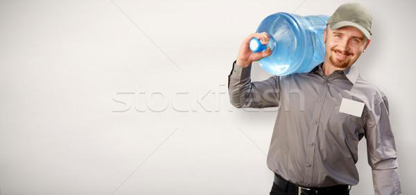 Férfi üveg ivóvíz víz házhozszállítás szolgáltatás Stock fotó © Kurhan