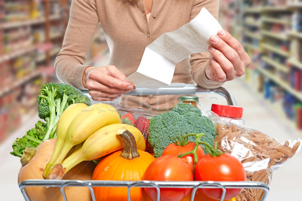 Woman with grocery receipt and shopping cart. Stock photo © Kurhan