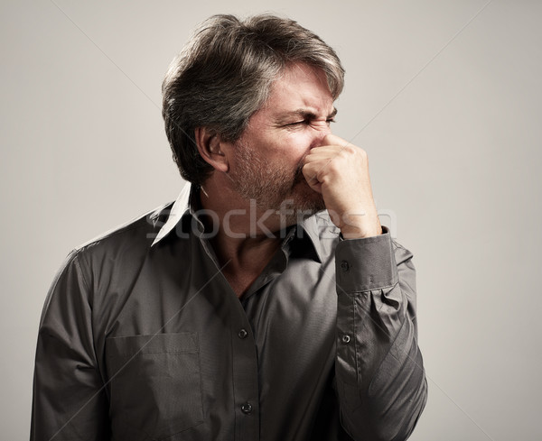 Man hiding his nose Stock photo © Kurhan