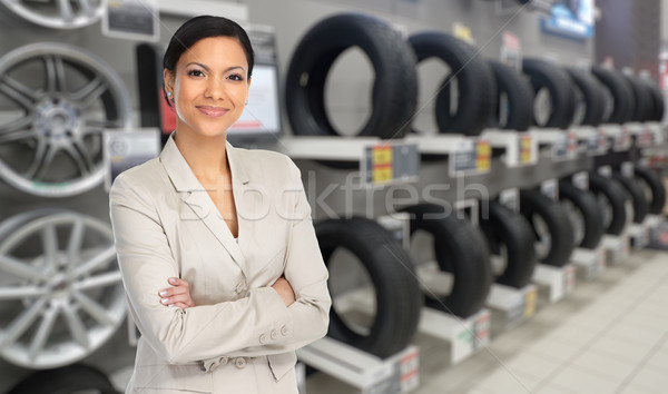 Auto dealer woman near a car tire. Stock photo © Kurhan