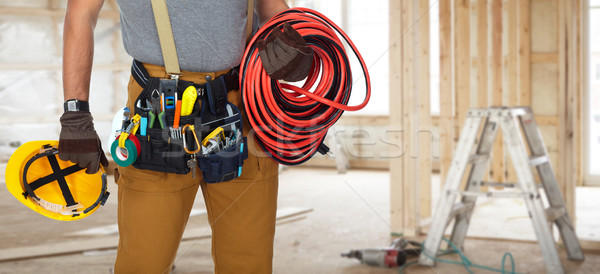 Stock photo: Electrician with construction tools and cable.
