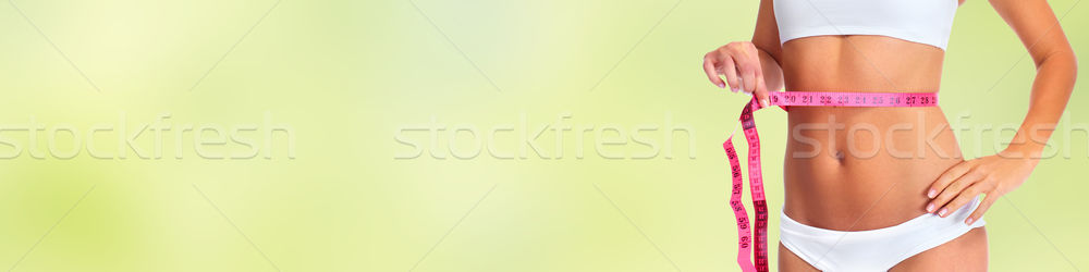 Woman waist with measuring tape over green background. Stock photo © Kurhan