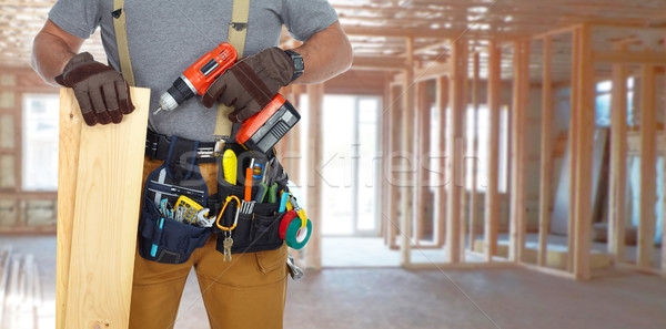Builder handyman with drill and wooden plank. Stock photo © Kurhan