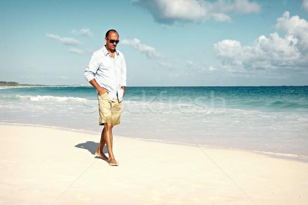 Férfi sétál homokos tengerpart jóképű férfi vakáció égbolt Stock fotó © Kurhan