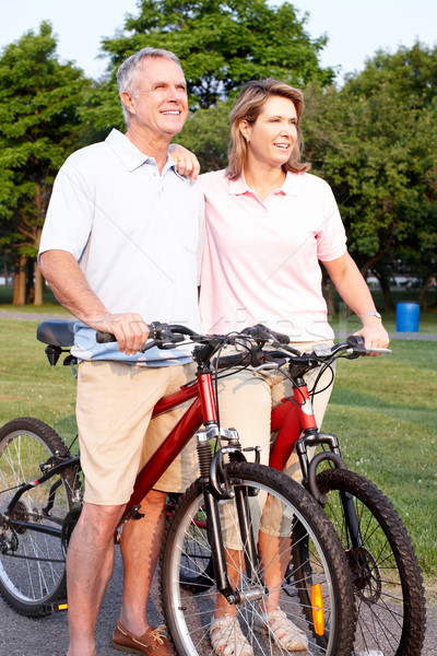 Senior couple cycling in park. Stock photo © Kurhan