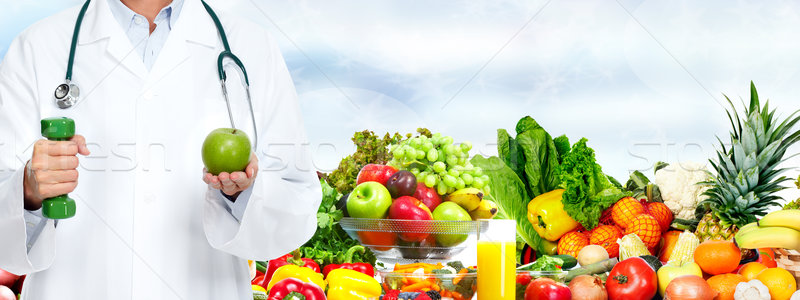 Stock photo: Doctor woman hands with apple and dumbbell.
