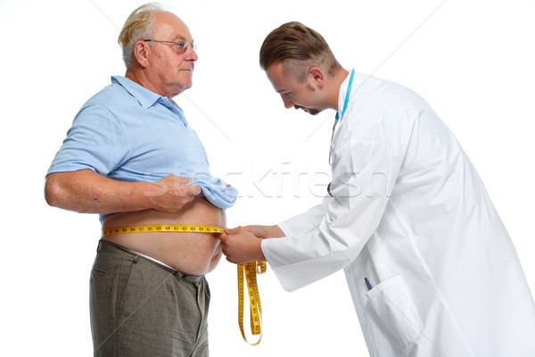Doctor measuring obese man body fat. Stock photo © Kurhan