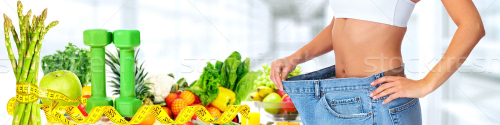 Slimming woman wearing big pants over blue background. Stock photo © Kurhan