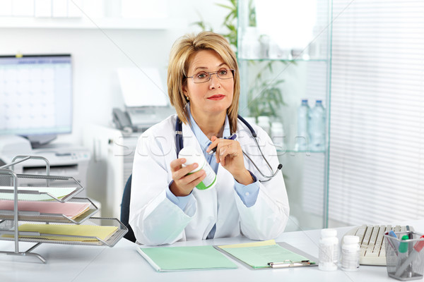 Stock photo: Mature doctor woman with pills.