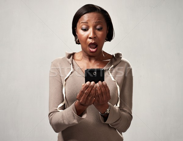 African surprised woman with smartphone Stock photo © Kurhan