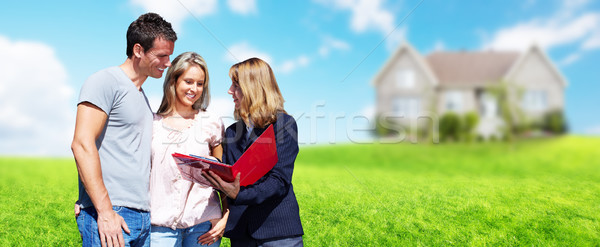 Real Estate agent woman with clients near new house. Stock photo © Kurhan