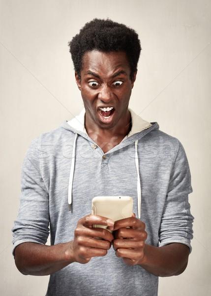Stockfoto: Zwarte · man · smartphone · verwonderd · afro-amerikaanse · jonge · man · mobiele · telefoon