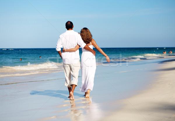 Romantic couple walking on beach Stock photo © Kurhan