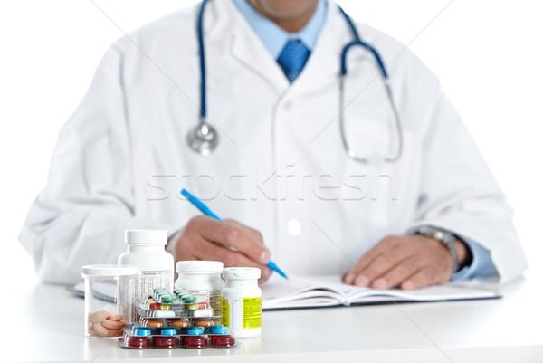 Doctor writing medical prescription. Stock photo © Kurhan