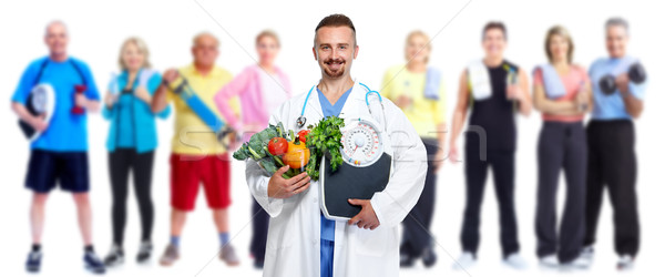 Doctor with vegetables and group of fitness people. Stock photo © Kurhan