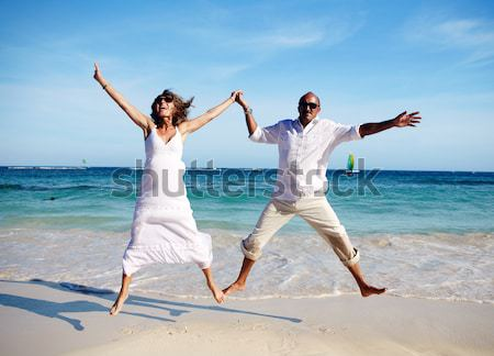 Stock photo: Happy couple jumping on beach