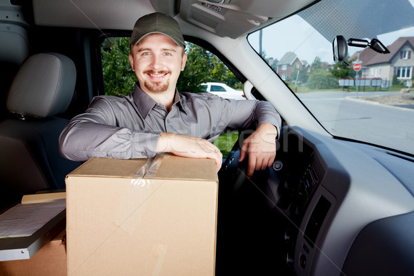 Young delivery man with a parcel. Stock photo © Kurhan