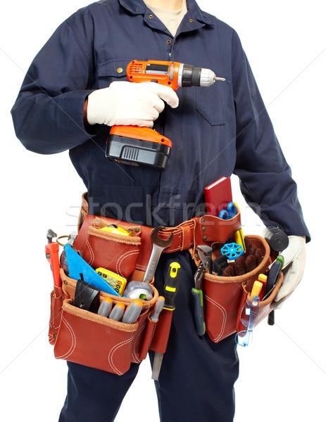 Handyman with a tool belt and drill. Stock photo © Kurhan