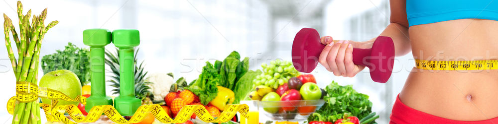 Woman abdomen with measuring tape over vegetables background. Stock photo © Kurhan