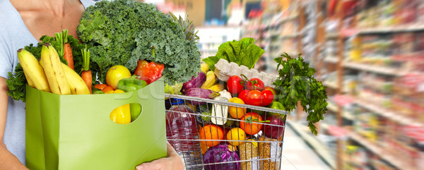 Stock photo: Woman with grocery bag of vegetables.