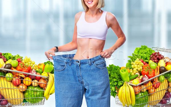 Slimming woman wearing big pants over blue background. Stock photo © Kurhan
