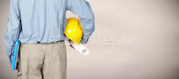 Engineer with helmet and blueprint. Stock photo © Kurhan