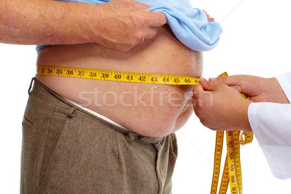 Doctor measuring obese man stomach. Stock photo © Kurhan