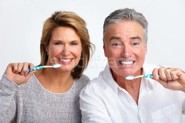 Stock photo: Happy elderly couple with toothbrush.