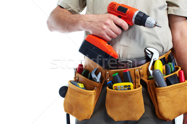 Handyman with a tool belt and drill. Stock photo © Kurhan
