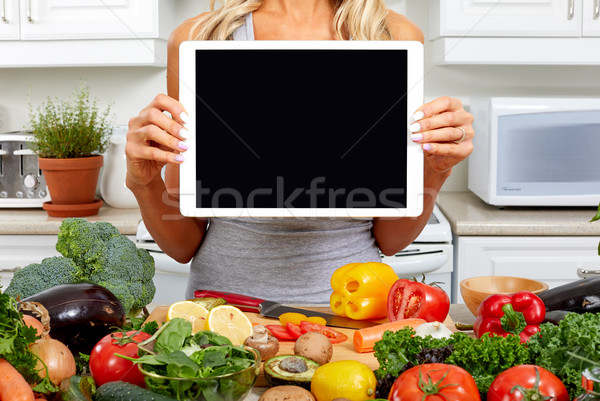Hands of woman with tablet in the kitchen. Stock photo © Kurhan