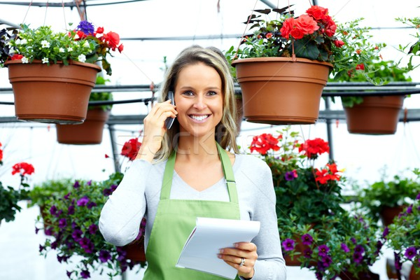 Stock photo: Florist woman working with flowers in greenhouse.