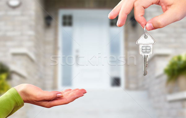 Hand with a key over new house background. Stock photo © Kurhan