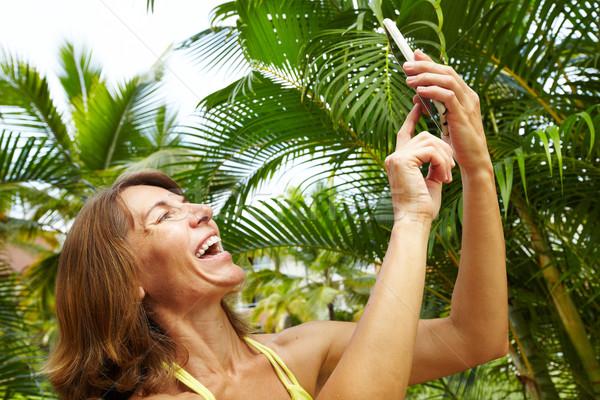 Donna smartphone tropicali giardino vacanze faccia Foto d'archivio © Kurhan