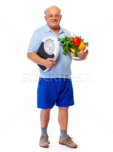 Senior man with scales and vegetables. Stock photo © Kurhan