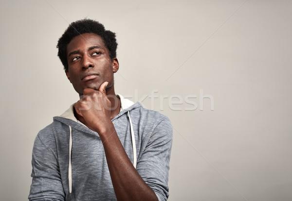 Myślenia Murzyn młody człowiek szary ściany Zdjęcia stock © Kurhan